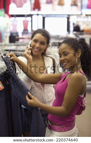 Two teen girls shopping for clothes - stock photo