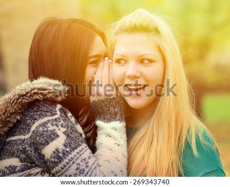Two teen girls whispering rumours - stock photo