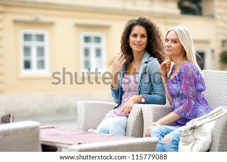 two teen woman friends having fun sitting in outdoor cafe - stock photo