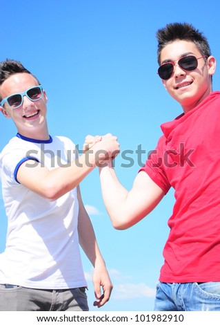 Two teenage boys shaking hands against blue sky - stock photo