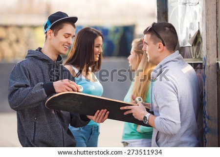 Two teenage boys trying to fix their skateboard while two girls talking in the background - stock photo