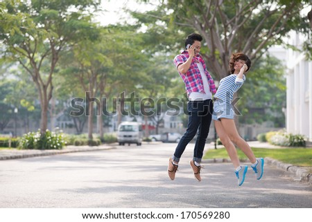Two teenage friends jumping with phones - stock photo