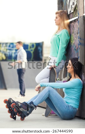 Two teenage friends with rollerblades and skateboard chilling in a skate park - stock photo