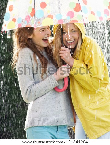 Two Teenage Girl Sheltering From Rain Beneath Umbrella - stock photo
