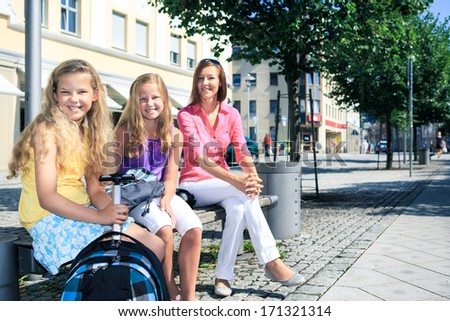 two teenage girls and their mother on the way to school - stock photo