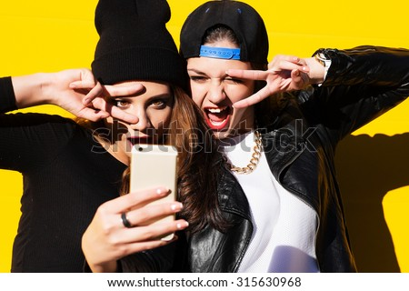 Two teenage girls friends in hipster outfit outdoors make selfie on a phone.  - stock photo