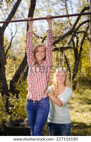 Two teenage girls having fun in park hanging on green countryside rural copy space background - stock photo
