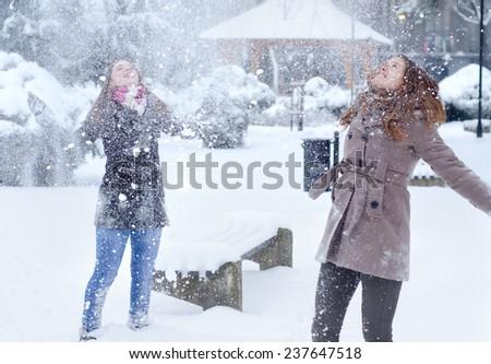 Two teenage girls having fun in the snow on beautiful winter day. - stock photo