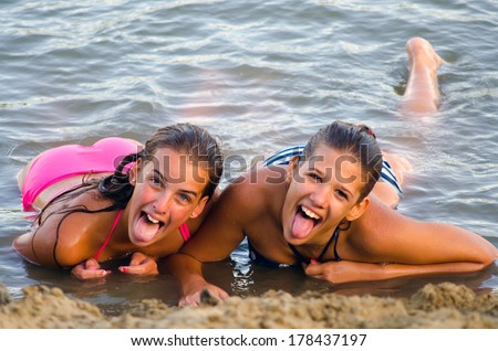 Two teenage girls having fun on the beach.