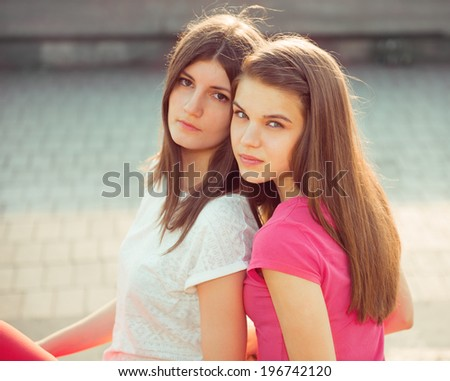 Two teenage girls having fun outside - stock photo