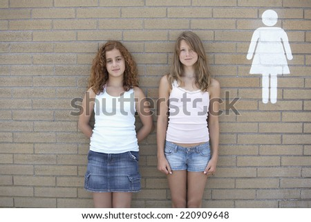 Two teenage girls leaning against wall next to restroom sign - stock photo