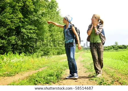 Two teenage girls looking into a forest on a mountain