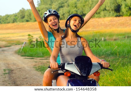Two teenage girls riding motorcycle on the countryside. - stock photo