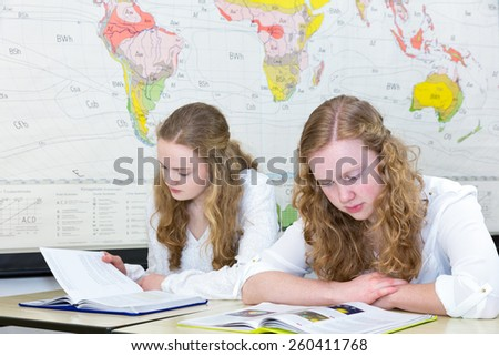 Two teenage girls studying in geography class in front of wall chart showing the world - stock photo