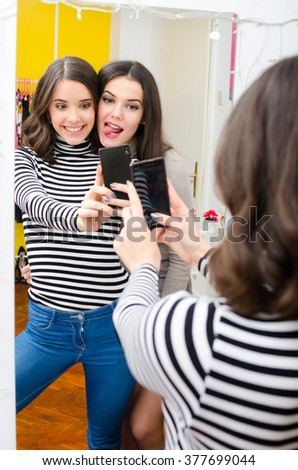 Two teenage girls taking selfie pictures in front of the mirror. - stock photo
