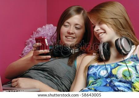 Two teenage girls use cellphone, laptop and a headset in their room.
