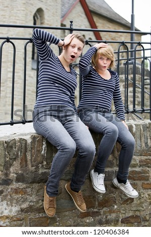Two teenage girls wearing the same dress and looking shocked - stock photo