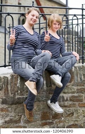 Two teenage girls wearing the same dress and showing peace sign - stock photo