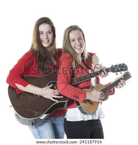 two teenage sisters have fun with ukelele and guitar in studio against white background