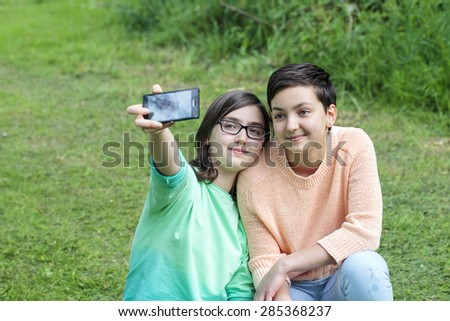 Two teenage sisters with the mobile phone