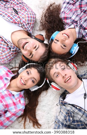 Two teenager couples listening to music with headphones on a carpet