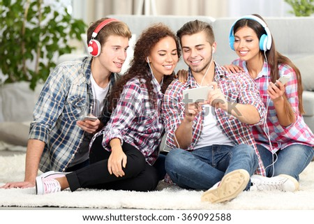 Two teenager couples listening to music with mobile phone in living room