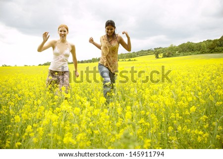 Two teenager girls friends running together on a large yellow flowers field during a summer vacation in the countryside on a sunny day, having fun. - stock photo