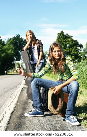 Two teenager girls hitch hiking on a desert road