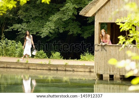 Two teenager girls relaxing by a wooden hut structure on a lake during a summer vacation in the forest, smiling and relaxing.
