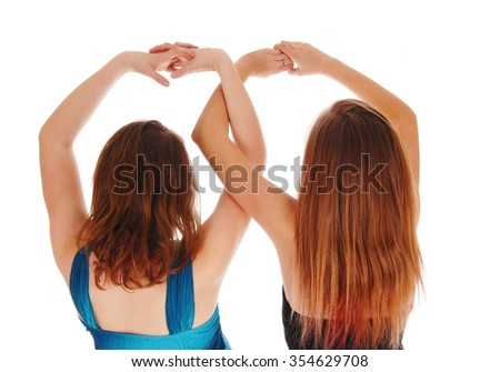Two teenager girls standing from the back holding there hands up in a closeup image, isolated for white background. - stock photo