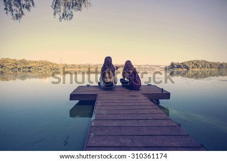 Two teenager girls with backpacks sitting on a pier at the river bank and the city in the background - stock photo