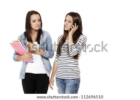 two teenager with exercising books and one is calling by smartphone on white background - stock photo
