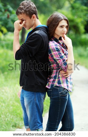 Two teenagers apart looking sad, breaking up - stock photo