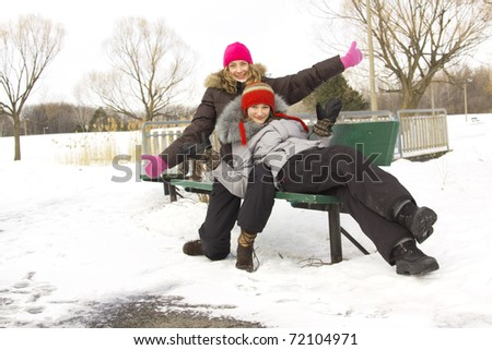Two teenagers best friends sit on a bench during winter season