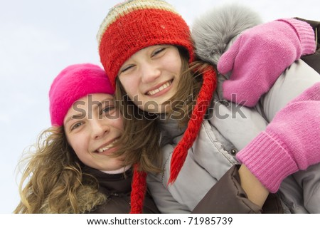 Two teenagers best friends with hats and winter coat smiling