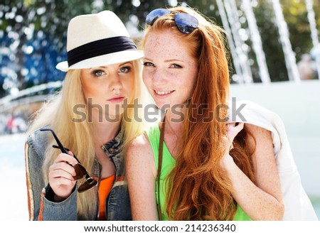 Two teenagers girl walking in city center - stock photo