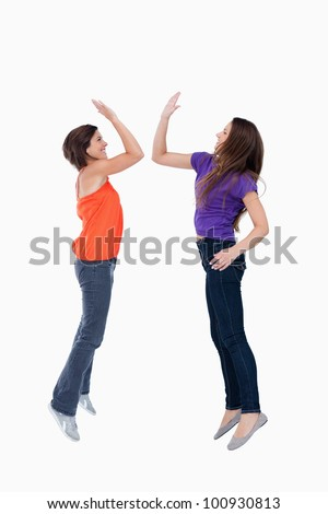 Two teenagers leaping while giving a high-five in the air