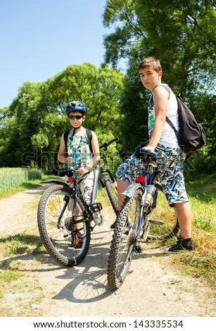 Two teenagers relaxing on a bike trip in sunny day