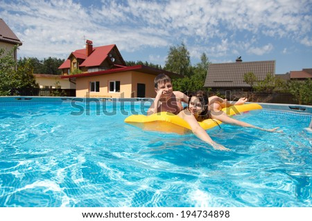 Two teenagers swimming in the pool in the hot summer - stock photo