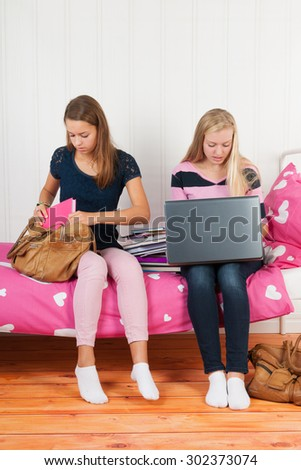 two teengirls sitting on bed making homework together with school books and laptop - stock photo