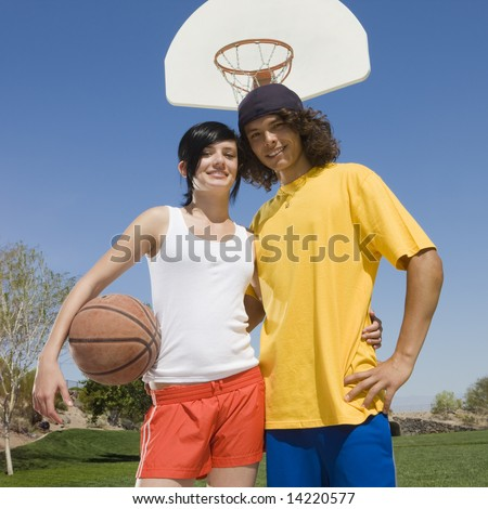 Two teens hang out at a park with a basketball