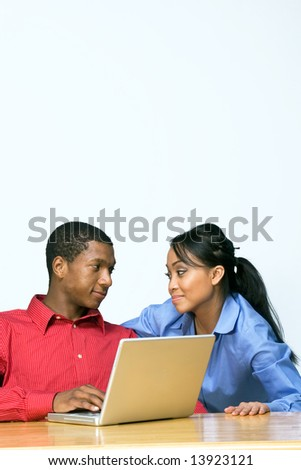 Two Teens looking at each other as he types on a Laptop Computer. Horizontally framed photograph - stock photo