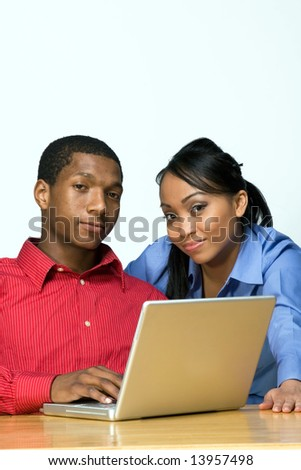 Two Teens Looking serious as they stare ahead and he holds a Laptop Computer. Horizontally framed photograph