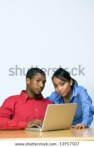 Two Teens looking serious as they stare ahead and he holds a Laptop Computer. Vertically framed photograph - stock photo
