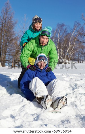 Two teens pushing their friend sitting on a snowboarder