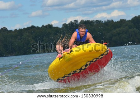 two teens tubing on a lake - stock photo