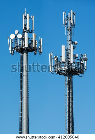 Two telecommunications towers with satellite dishes and antennae fro transmitting and receiving broadcasting signals against a sunny blue sky with copy space - stock photo