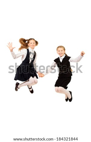 Two ten years girls in a uniform jumping for joy. Isolated over white. - stock photo