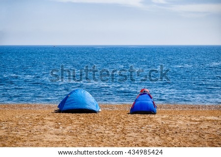 Two tents on beach by Mediterranean sea. - stock photo
