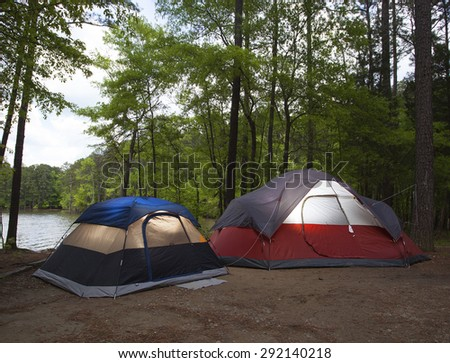 Two tents pitched by a lake with nightfall soon to arrive - stock photo